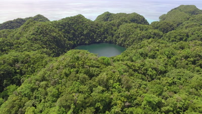 Aerial drone shot over jungle covered island reveals Marine Lake