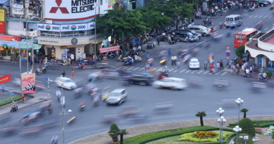 Ho Chi Minh / Saigon, Vietnam. Vietnamese city with traffic and crowds of people on the streets of downtown Saigon, Vietnam, traveling on scooters,  cars or walking on sidewalk in this busy metropolitan asian city.