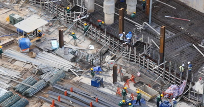 Asia growth building and office construction site development with engineer, architect and labourer men working laying concrete,  cement and steel structures on Bitexco 'The ONE' towers Ho Chi Minh / Saigon, Vietnam.