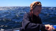 Dolphins And Gannets Feed On Sardine Run Behind Young Woman On Boat