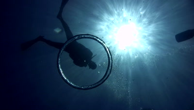 Bubble ring against sun with diver silhouette