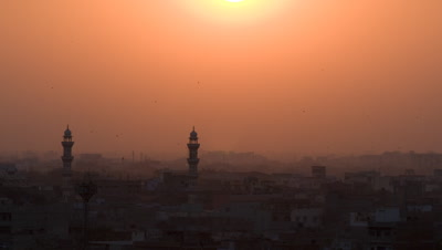 Wide angle establishing shot over Jaipur's traditional rooftops busy with birds as hazy orange sun dips and sets over dusty skyline,India