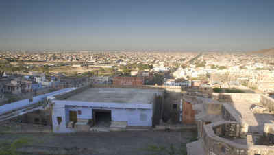 Wide angle overlooking Jaipur from high point as night becomes day and shadows move over city until all lit by full sun, India