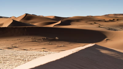 Medium wide angle desert dune landscape with sand blowing in foreground as shadows move over throughout the day and night falls