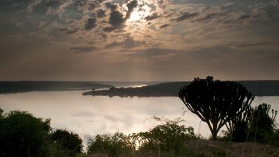 Wide angle sunrise over Lake Edward with god rays and euphorbia