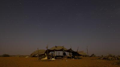 Medium wide angle night falls over Tuareg desert nomad tent and stars move through the sky