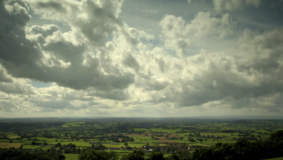 Slow pan right to left as clouds sweep towards camera over countryside. Taken from high viewpoint on Mendip Hills overlooking Somerset Levels, UK