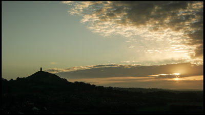 Glastonbury Tor at sunrise as clouds sweep past away from camera.