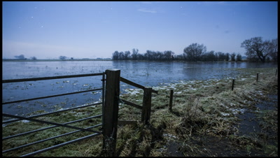 Flooded field at night with gate and ditch in foreground. Frost forming on foreground grasses and ditch. Moon shadows and mist swirling, occasionally onto lens, winter, Somerset, UK