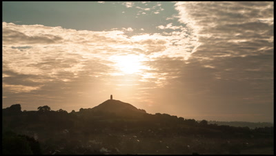 Panning right to left as dawn clouds slowly part to reveal sun over Glastonbury Tor, a landmark of mystical significance in Somerset, UK