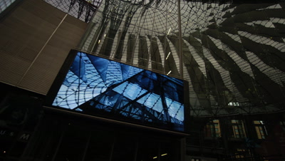 Medium wide angle looking upwards at large tv screen inside the innovative architecture of the highly modern Sony Centre Berlin, Germany