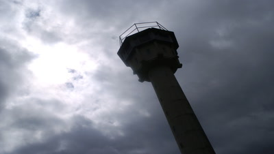 Low angle looking up to stormy cloudy sky featuring former East German watchtower in silhouette in the foreground outside Moedlareuth in Germany