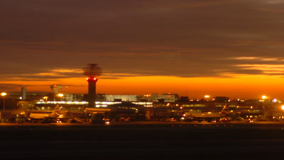 Medium wide angle London Heathrow Airport Terminal building with planes mainly static and vehicles moving to and fro servicing planes with orange sunset sky, UK