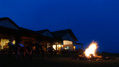Mid shot exterior of Mweya African Safari Lodge building as campfire set, lit, then people come to sit around it as evening becomes night in Queen Elizabeth National Park, Uganda