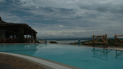 Medium wide angle Mweya African Safari Lodge swimming pool with grand view over vast savannah landscape and dramatic cloudscape in Queen Elizabeth National Park, Uganda