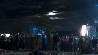 Medium wide angle audience watching band on stage at the The Big Chill with full moon and scudding clouds overhead Ledbury Castle UK