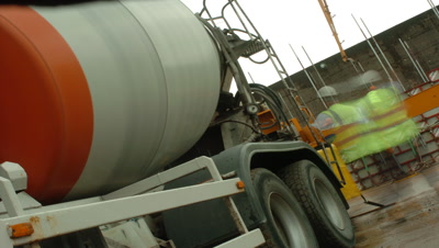 Mid shot cement mixer at building site, camera at 45 degree angle, lorry departs and returns, UK