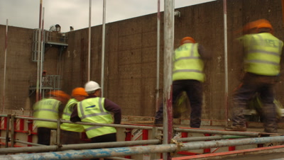 Mid shot construction workers spreading cement UK