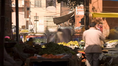 Mid shot bustling market stall with people coming and going in Jaipur India