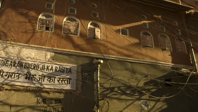 Mid shot shadows move over tangle of electric wires and typical old painted Jaipur building with shutters India