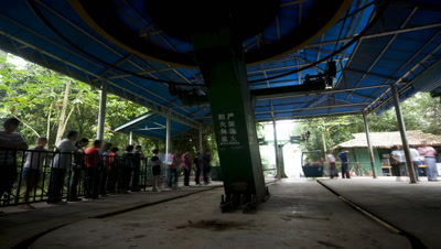 Medium wide angle cable car station in Wild Elephant Valley China with people queuing up and getting into cars