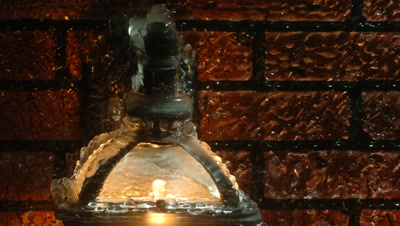 Close up of ice forms on top of lit outside lantern -black old fashioned- with red brick background