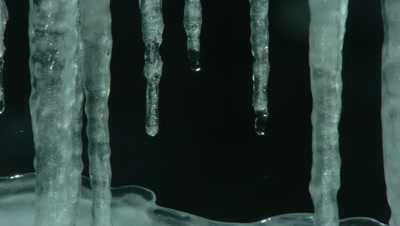 Close up of Icicles drop down from top of frame against black background and ice rises up from bottom of frame to fill about one third