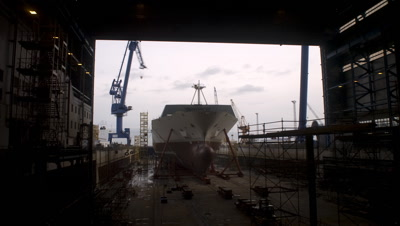 Medium wide angle looking from boat shed to outside dry dock where robots are assembling ship in Aker Ship yard Germany