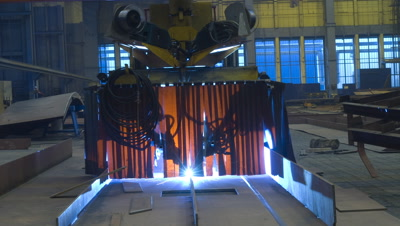 Mid shot welding robot moves towards camera over sheet metal for ship construction curtain obscures welding light in Aker Ship yard Germany