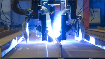 Mid shot welding robot moves directly to camera and completes two sequences of welds on steel in Aker Ship yard Germany