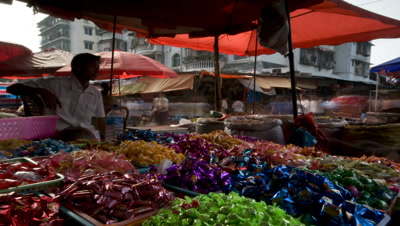 Wide angle sweet seller at food market with brightly coloured sweets in tubs in foreground and busy market behind in Xinghong China