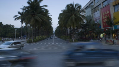 Medium wide angle intersection of busy palm tree lined street with chinese posters featured in Xinghong, China