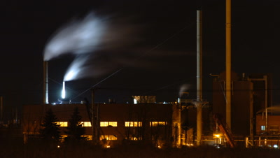 Mid shot Esso oil refinery at night with streaming clouds from chimneys Montreal Canada