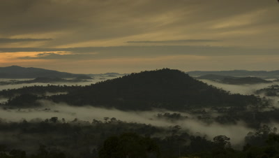 Wide angle panning view as move over densely forested landscape with mountains and boiling clouds in the valleys with soft evening or morning sky Borneo