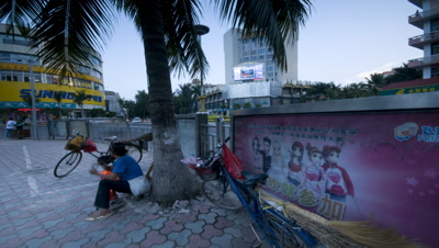 Mid shot busy street corner with palm tree and lady sat on sidewalk beneath it featuring Chinese poster Xinghong China