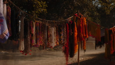 Mid shot brightly coloured beaded necklaces and scarves hanging on lines by track in market with people passing by, Sonpur, Bihar, India