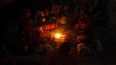Mid shot people sitting in circle on ground with small campfire making offerings and lighting incense, Sonpur, Bihar, India