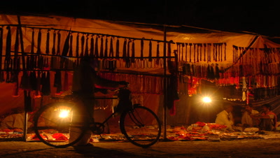 Medium wide angle lantern-lit roadside stall selling necklaces hanging up, strong silhouette bicycle arrives, stops and goes again, Sonpur, Bihar, India