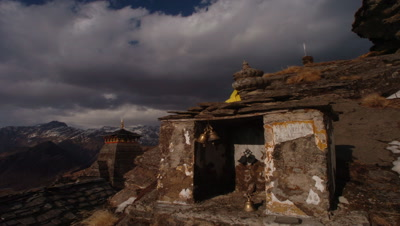 Mid shot Tungnath Temple in foreground with boiling storm clouds and Himalaya backdrop, Kedernath, India