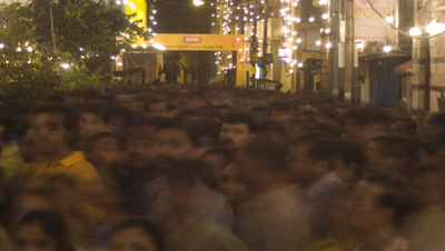 Medium wide angle over heads of densely packed people as they stream through a floodlit street during the festival of Durga Puja