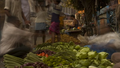 Mid shot busy roadside vegetable vendors selling to customers with backdrop of street traffic