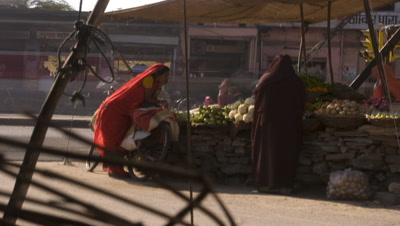 Medium wide angle vegetable market stall featuring stationary woman leaning on bicycle with other women in saris visiting stall