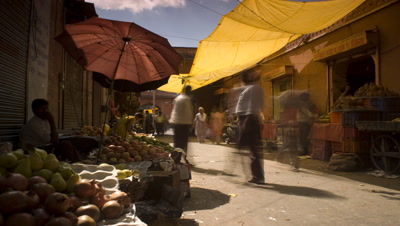 Medium wide angle panning shot in food market from one side of market to the other across busy pathway