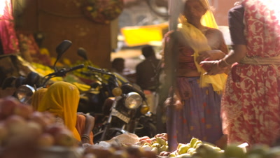 Close up colourfully dressed women buying and selling pears and fruit at market stall with motorbikes parked behind
