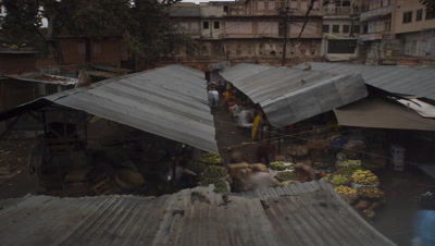 Medium wide angle panning shot over roofs of vegetable market as traders set up their stalls