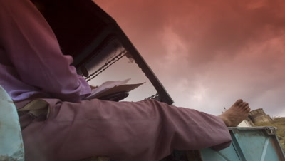 Close up side view of man sitting in tuk tuk looking at paperwork with gathering monsoon clouds