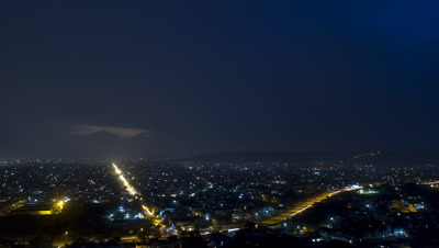 Wide angle overlooking Jaipur city from hill top featuring two main roads streaming with traffic and lightning