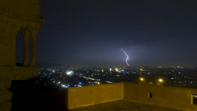 Wide angle overlooking Jaipur from hill top with temple building and featuring lightning over city