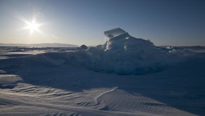 Close up sea ice with sunlight and shadows moving over with expansive sea ice at Grise Fjord in background