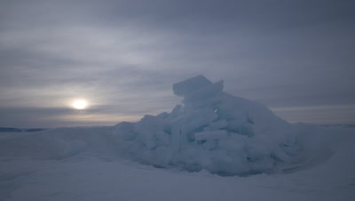 Close up sea ice with cloudy arctic sun dipping behind ice at Grise Fjord